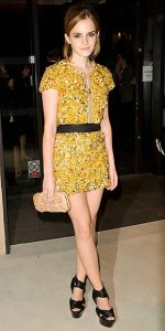 Emma Watson arrives at London Fashion Week wearing a gold Burberry mini dress.