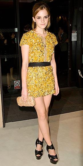 Emma Watson arrives at London Fashion Week wearing a gold Burberry mini dress.