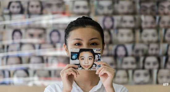 Daisy Tse, a customer of face reader Li Chau-jin, holds up a photograph of herself showing her eyebrow shape before and after having them plucked.