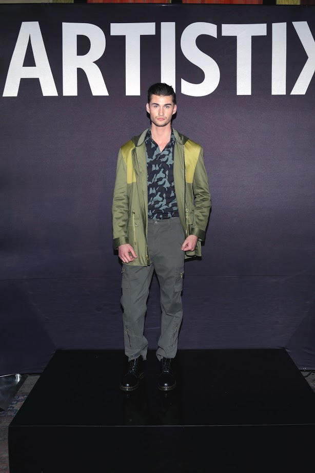 Look # 5. Nick- ARTISTIX Camo Woven; Military Rain Coat; Signature Khaki Chino (Photo by Lars Niki/Getty Images for ARTISTIX)